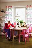 Woman sitting on pink-painted chair at round table below window with floor-length, floral curtain