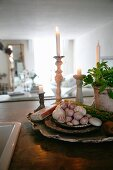 Bulbs of garlic on stacked dishes in front of lit candles in candlesticks