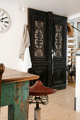 Bar stool with bicycle seat next to table and fitted cupboard with carved door panels made from dark wood