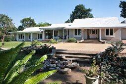 Drei aneinandergereihte, erdgeschossige Cottages mit Veranda davor grosszügiger Garten mit Palmen