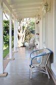Weisser Rattanstuhl an Hauswand auf Cottage-Veranda mit weisser Holzkonstruktion