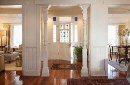 Blick vom Foyer in Hauseingang mit weissen Holzsäulen und Haustür mit bunten Gläsern, teilweise sichtbarer Wohn- und Essbereich in elegantem renoviertem Cottage