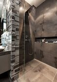 An open rain shower with dark tiles and a glass partition wall with limestone relief tiles behind the sink