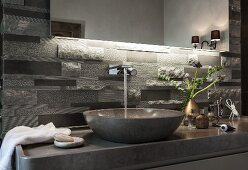 An illuminated mirror above polished limestone washstand with a console basin and grey limestone relief tiles