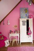 White wardrobe and console table with curved legs against pink-painted gable wall in vintage-style girl's bedroom