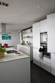White kitchen with island counter and dark grey tiled floor