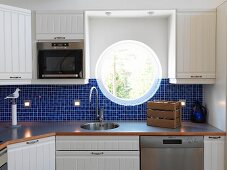 Porthole window above sink in Scandinavian kitchen with blue mosaic tiles