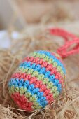 Striped, crocheted Easter egg amongst hay