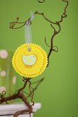 Hand-crafted, yellow felt rosette with Easter motif hanging from branch