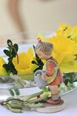 Vintage-style figurine of girl and narcissus flowers in glass bowl