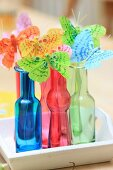 Butterfly decorations in colourful bottles on tray