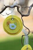 Hand-crafted, yellow felt rosettes with Easter motifs hanging from branch