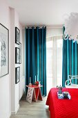Candles on whimsical side table, blue and black striped curtains and red bedspread in comfortable bedroom