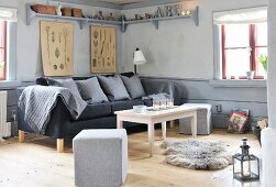 Pouffe, grey sofa, coffee table and animal-skin rug in corner of grey-painted living room with wooden floor