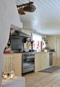 Rustic, cream kitchen counter with stainless steel gas cooker and white, wooden ceiling