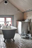Free-standing, vintage bathtub on glazed, tiled floor in attic bathroom with window in gable wall