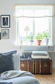 Blick über Sofa auf alte Truhe aus Leder vor Fenster, mit Tischleuchte und Blumentöpfen auf Fensterbank