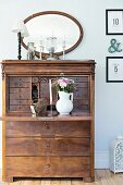 Old bureau with bouquet in white jug on fold-down desk in rustic interior