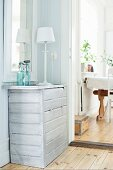 weiße Tischleuchte auf Kommode, hell lasiert, in Zimmerecke neben offenem Durchgang