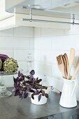 Zimmerpflanze neben weißem Porzellankrug mit Holzlöffeln und Schale mit Artischocke auf Tisch, in Zimmerecke