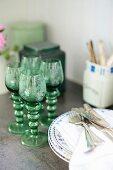 Alte Weinrömer Gläser neben Tellerstapel mit Besteck