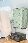 Old basket painted pastel green hung on wall above vintage, leather suitcase next to bed