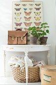 Alte Aktentasche und Geranientöpfe vor Tafel mit Schmetterlingsabbildungen auf halbkreisförmigem Wandtisch, weiss lackiert, darunter Wäschekorb