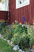 Blumenbeet mit Steineinfassung vor Holzhaus, rotbraun gestrichen