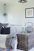 Kerzenhalter mit weissen Kerzen auf Vintage Holzkiste neben Tagesbett in schlichter Zimmerecke