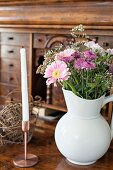 Bouquet of summer flowers in white china jug and candle in copper candlestick