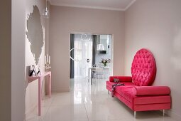 Deep pink couch with round backrest and pale pink console table below mirror in elegant modern foyer