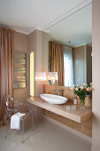 Luxurious bathroom with glossy washstand counter, mirrored wall, designer table lamps and Ghost chair