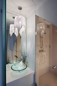 Elegant bathroom with shower, tall mirror and pendant lamp with glittery fabric lampshade