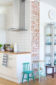 Retro child's chair and step stool painted turquoise between modern kitchen counter with stainless steel extractor hood and glass display cabinet