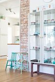 Retro child's chair and step stool painted turquoise against strip of exposed brickwork and next to crockery in glass display case