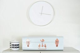 Purist wall clock above retro, suitcase-style bread bin and chain pot with graphical pattern