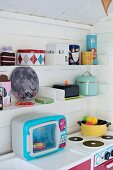 Colourful, retro play kitchen in Scandinavian playhouse
