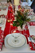 Table set for Christmas dinner with lit tealights in holders