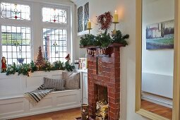 Open fireplace with brick surround and window seat with Christmas decorations on windowsill