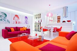 Open-plan living area in shades of bright red and orange with green, red and purple portraits on wall