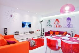 Open-plan living-dining room with bright red and orange elements in white interior and green, red and purple portraits on wall
