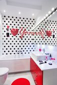 Heart and lipstick motifs on bathroom wall with black polka-dots in modern, white bathroom with red accents