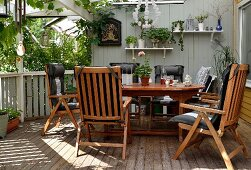 Wooden chairs with black seat cushions around table on veranda with wooden floor