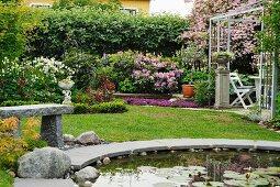 Rundes Wasserbecken mit Seerosen im Vordergrund in sommerlichem Garten