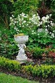Pflanzgefäss mit Figur in blühendem Garten