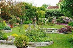 Staudenbeete mit Steineinfassung und runder Teich in sommerlichem Garten