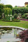 Runder Teich mit Seerosen in sommerlichem Garten