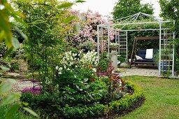 Rundes Beet mit niedriger Hecke im Garten, im Hintergrund Metallpavillon und Hollywoodschaukel