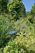 Nostalgische hellblaue Gartenbank in sommerlicher Gartenanlage
