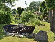 Traditionelles Holzboot auf Findlingen in sommerlichem Garten